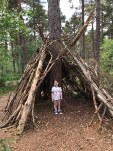 Child hiding in a log shelter